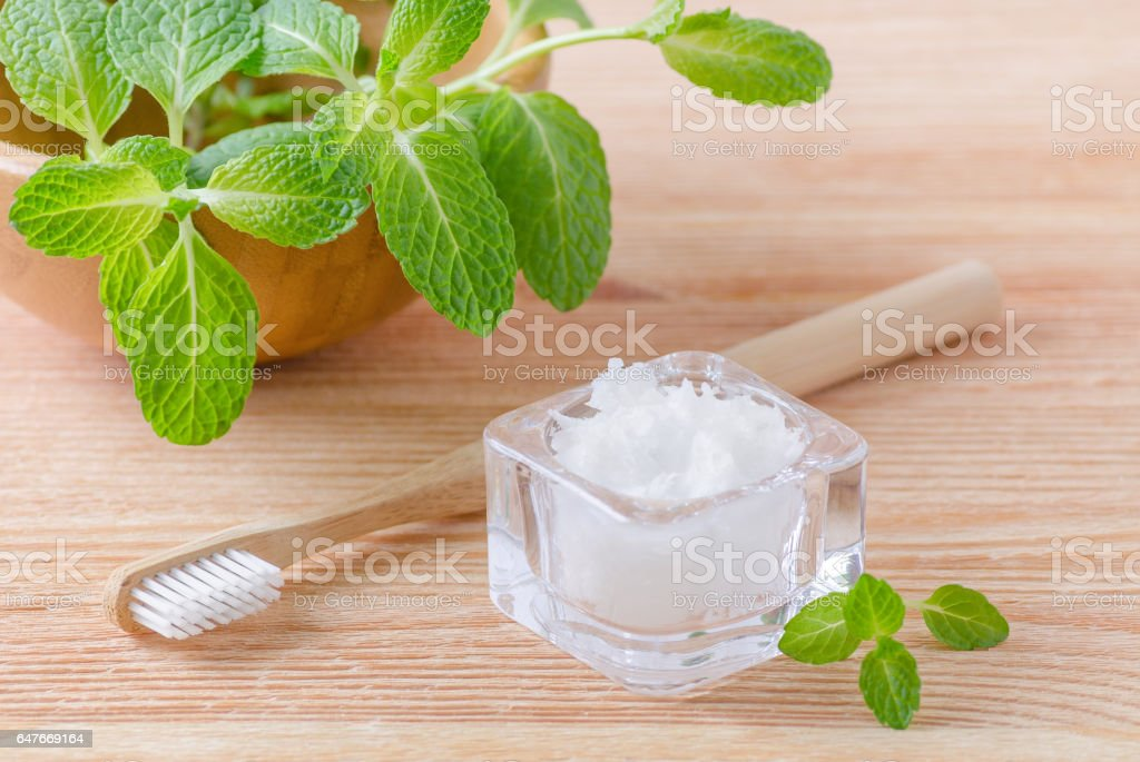 alternative natural toothpaste coconut oil and wood toothbrush closeup, mint on wooden stock photo