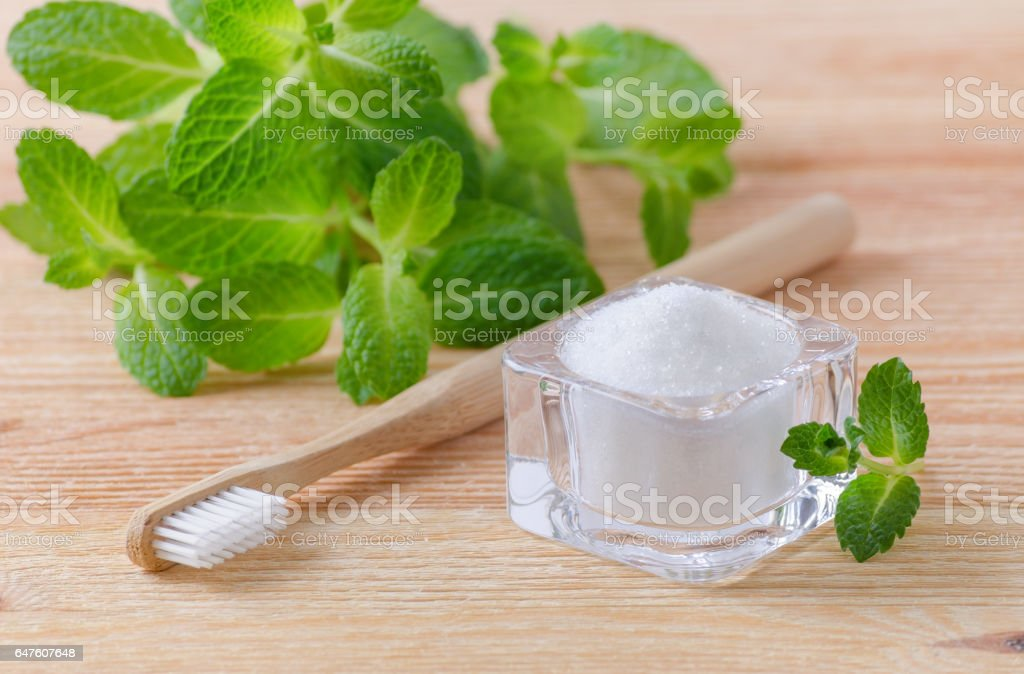 alternative natural toothpaste xylitol, soda, salt, and wood toothbrush, mint on wooden stock photo