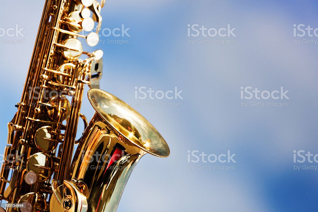 Alto sax close up against sky with scattered clouds stock photo