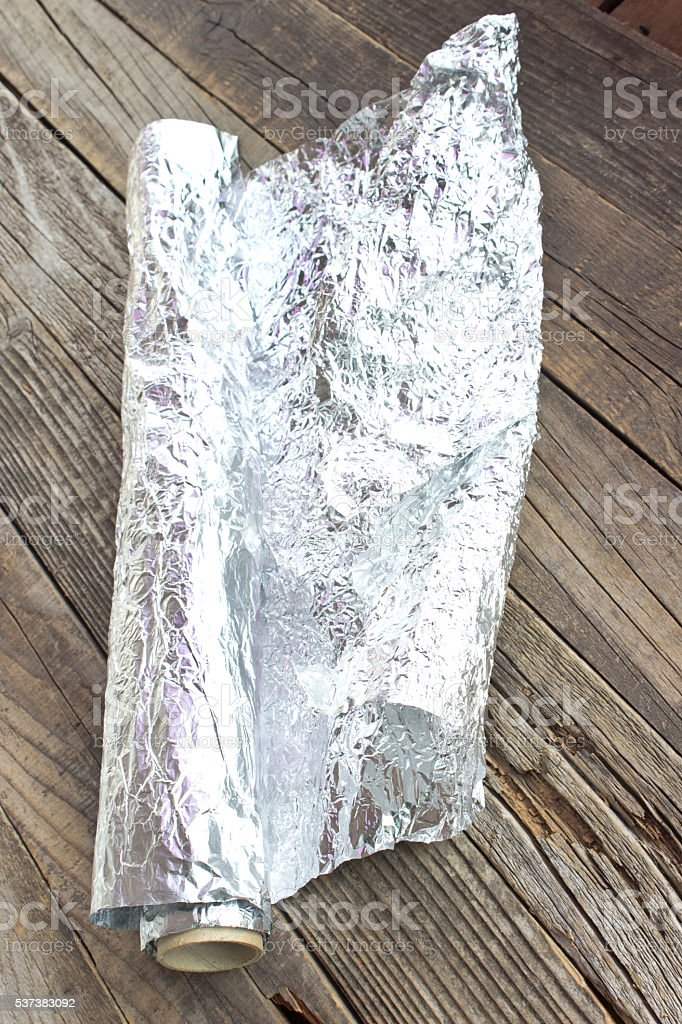 Aluminum foil on wooden background stock photo