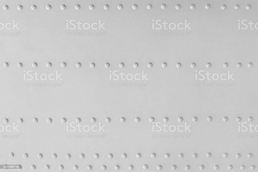 Aluminum plate with several rows of rivets as a background stock photo