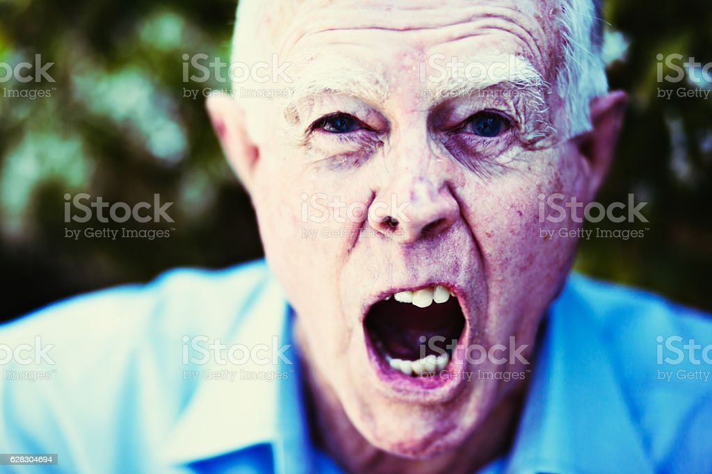 Alzheimers or simply angry? Very grumpy old man shouting. stock photo