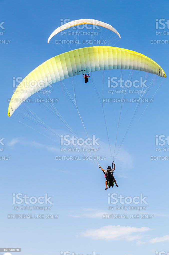 Amateur paragliders in blue sky with clouds stock photo