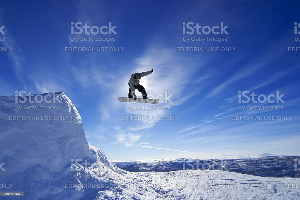 Amateur snowboarder making a grab in big air jump. stock photo