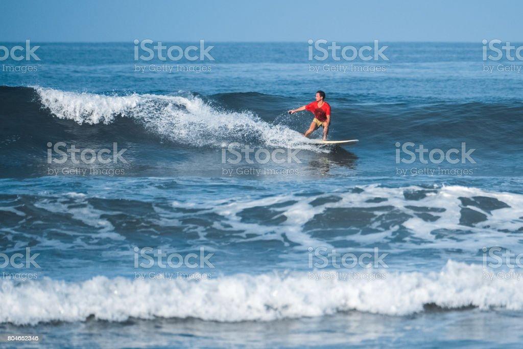 Amateur surfer rides the wave stock photo