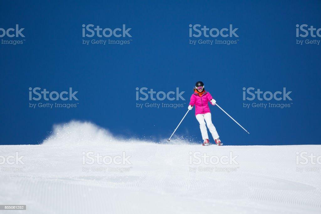 skiing woman on ski piste with dark blue sky, Obertauern, Salzburg,...