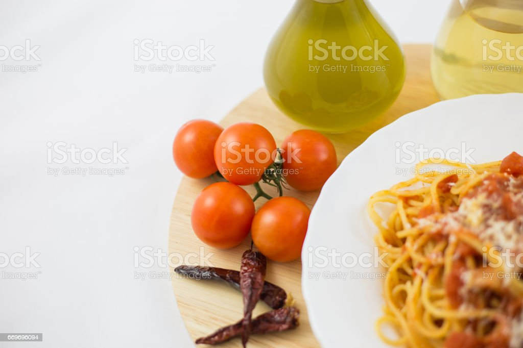 Amatriciana pasta and ingredients, such as bacon, cheese, tomato, pepper and chili. stock photo