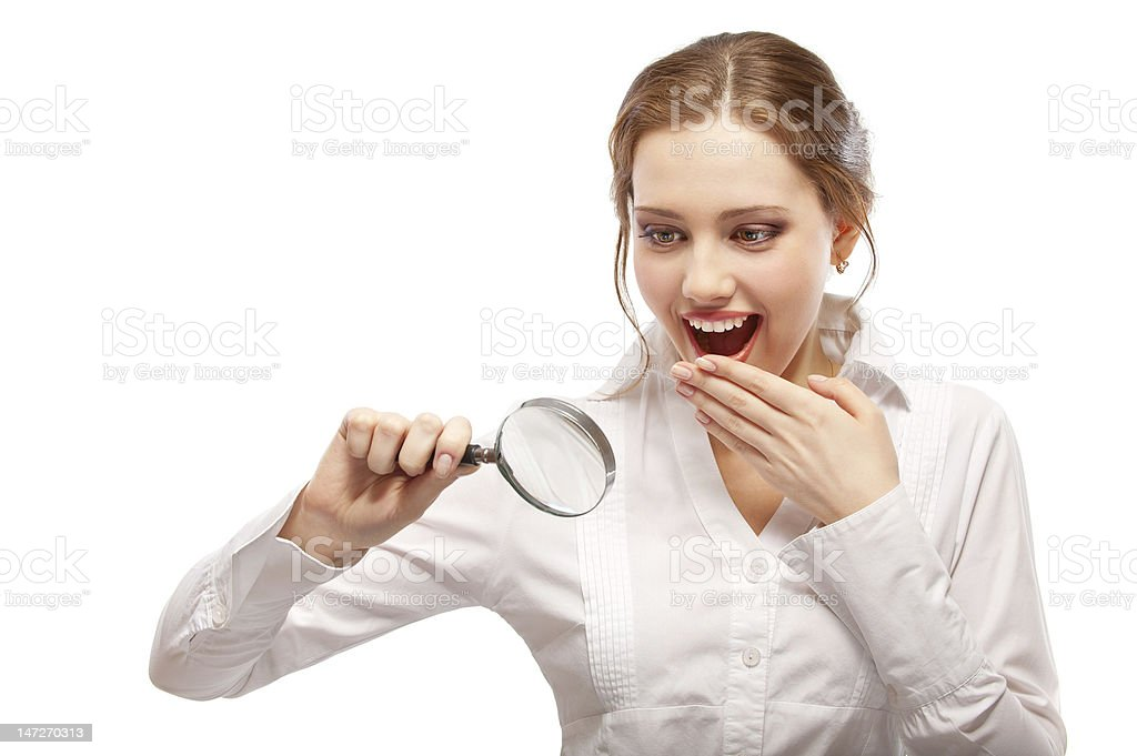 Amazed girl looks through magnifier royalty-free stock photo