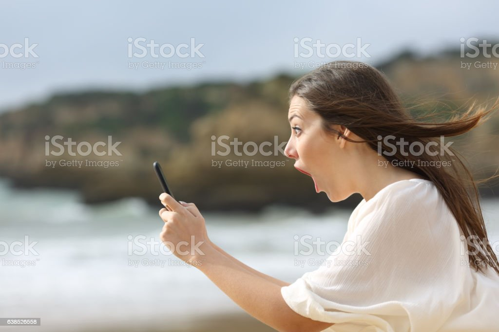Amazed girl with her smart phone stock photo
