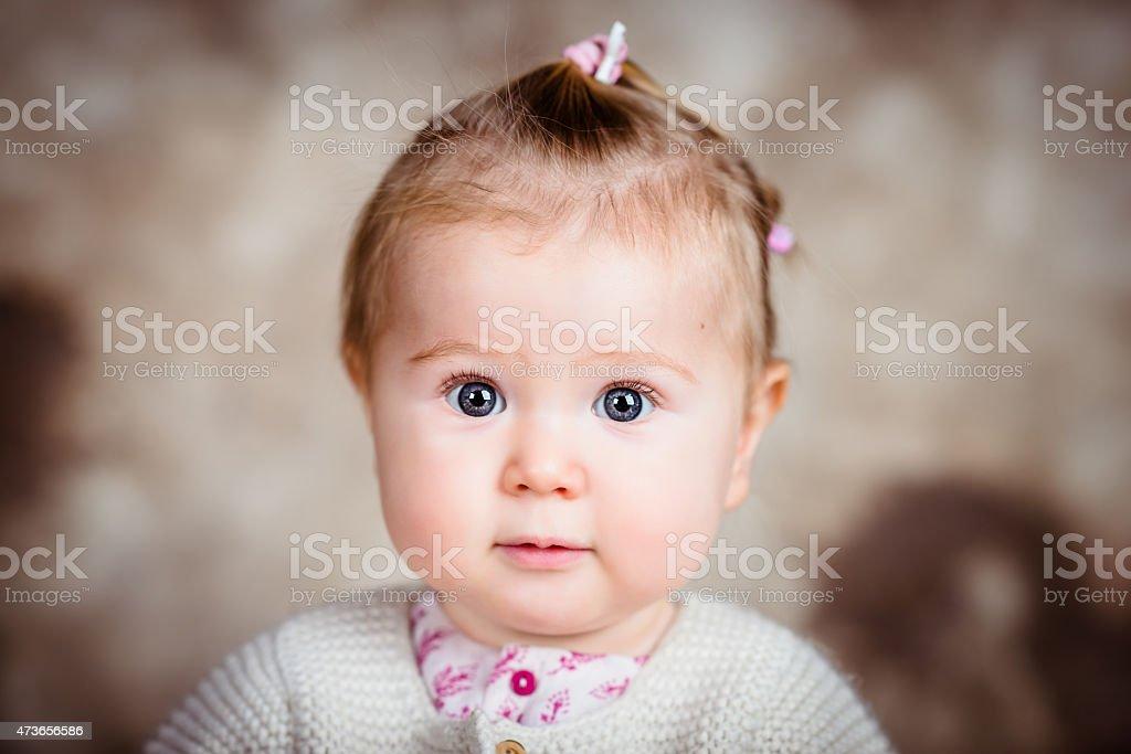 Amazed little girl with big grey eyes and plump cheeks stock photo