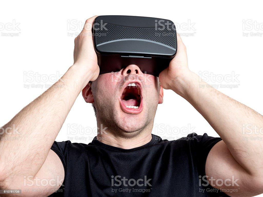 Amazed man using virtual reality glasses isolated on white background stock photo