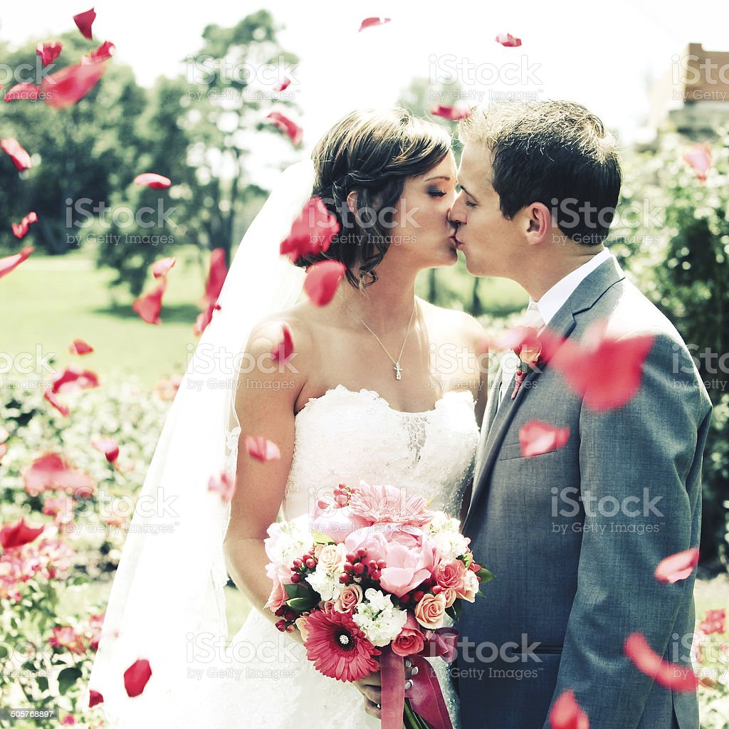 Amazing Bride and Groom Kissing Wedding Dress Flowers stock photo