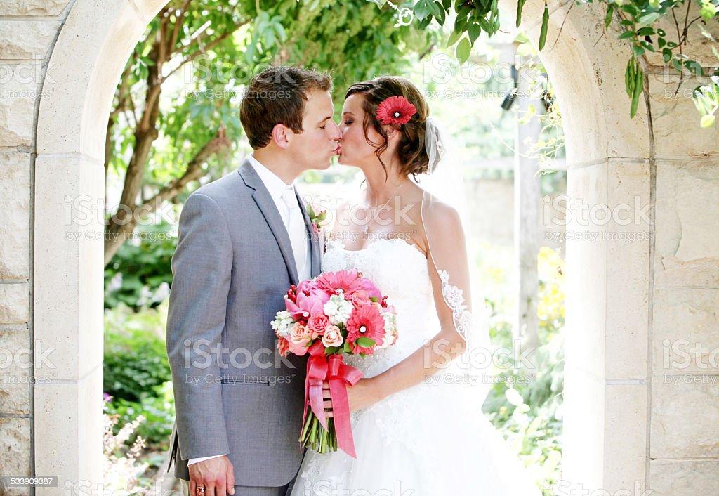Amazing Bride and Groom Kissing Wedding Dress Flowers stock photo