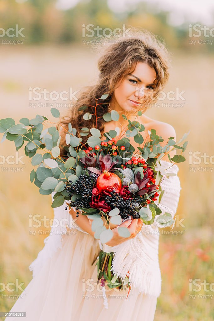 Amazing bride with bouquet of autumn fruits posing for camera stock photo