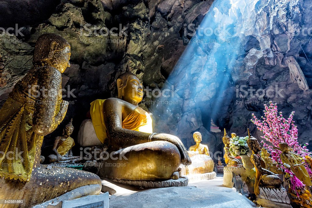Amazing Buddhism with the ray of light in the cave stock photo
