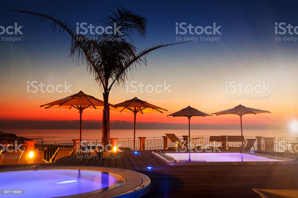 Amazing dawn with palm tree and parasols stock photo