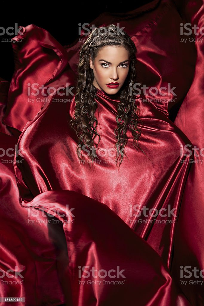 Amazing fashion model posing in red satin dress stock photo