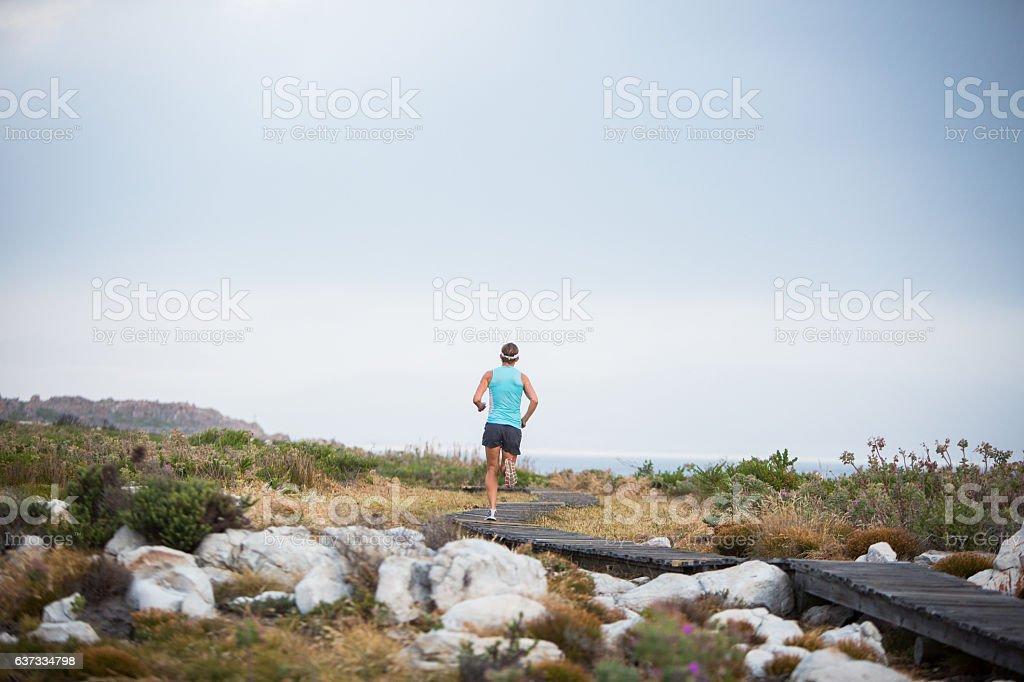 Amazing late afternoon run along a coastal path stock photo