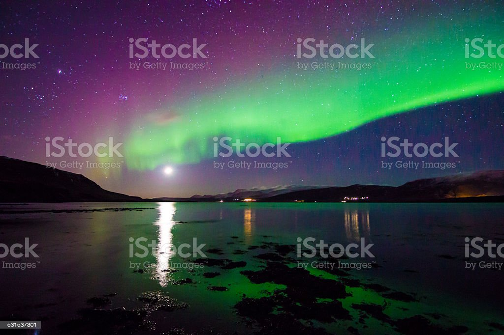 Amazing Moonset and celestial Aurora Borealis in Iceland's winter sky stock photo