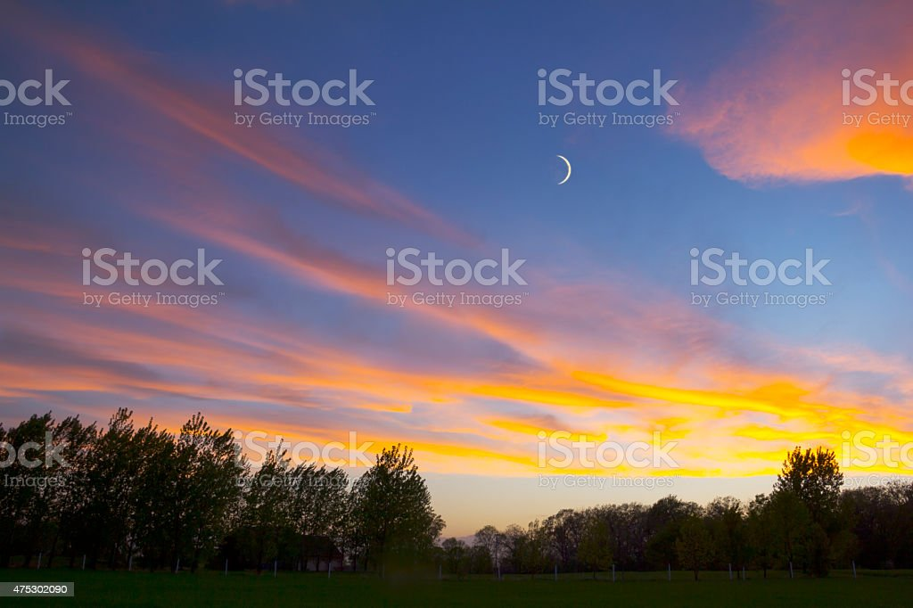 Amazing Spring Sunset With Crescent Moon stock photo