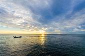 Amazing sunrise with silhouette image fishing boat