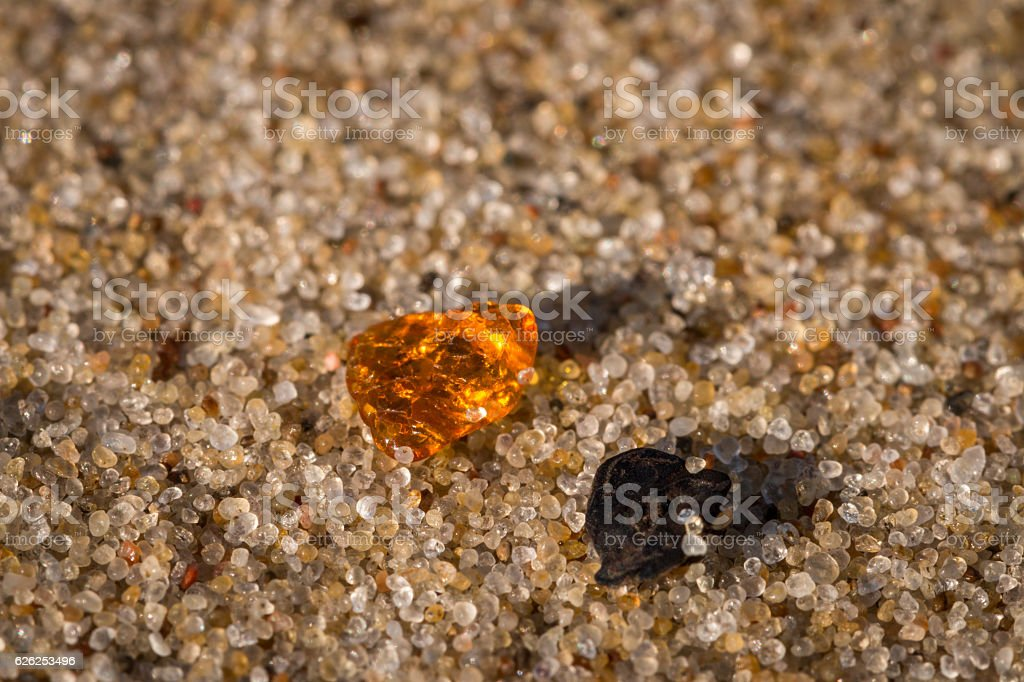 Amber and black stone on the sand grains stock photo