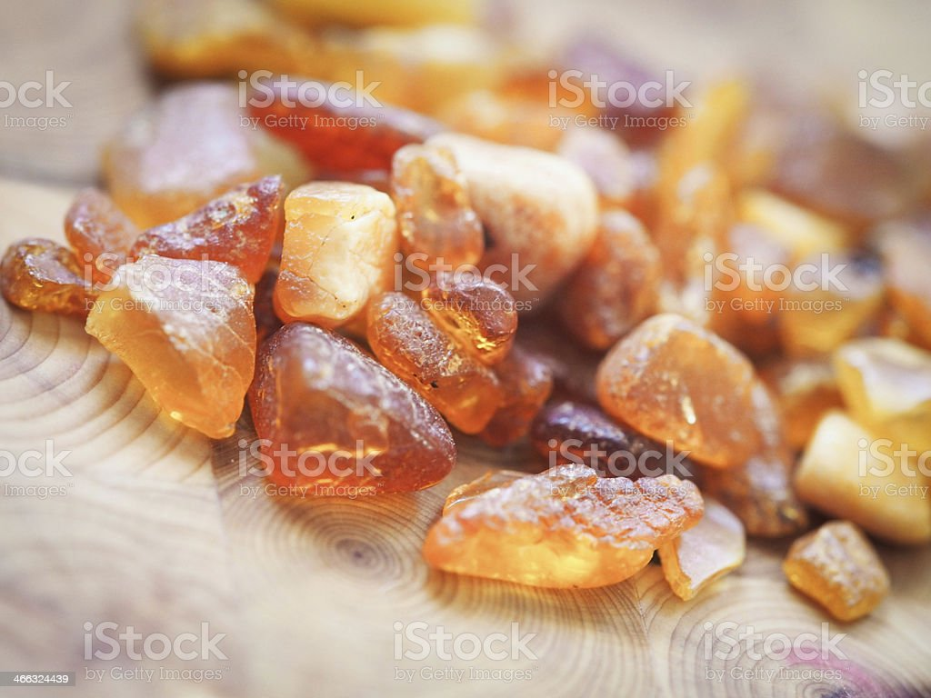 Amber crystals in pile on wood stock photo