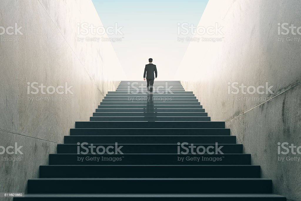 Ambitions concept with businessman climbing stairs stock photo