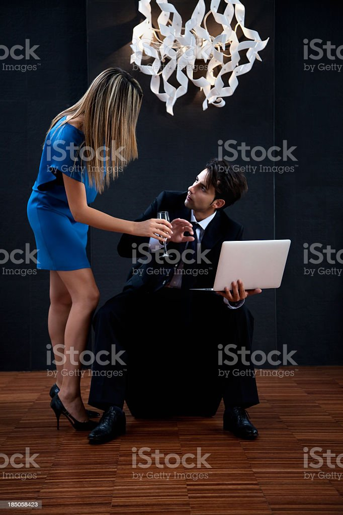 Ambitious businessman with a laptop resisting temptation. royalty-free stock photo
