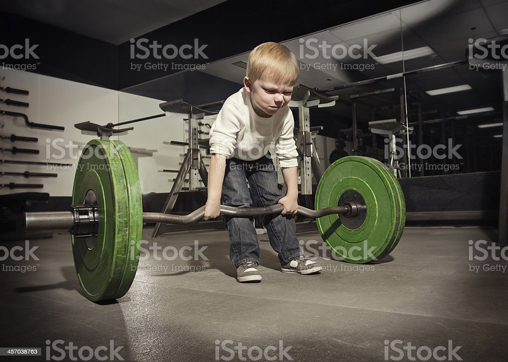 Ambitious, Determined little boy trying to lift stock photo