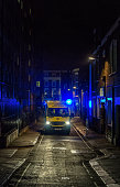Ambulance at night on narrow city centre street