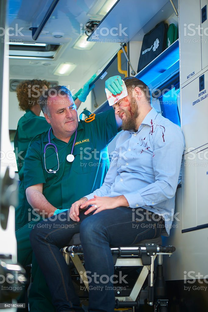 ambulance crew dealing with assault victim stock photo