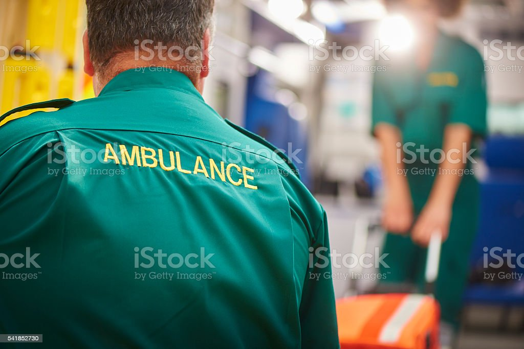 ambulance crew pulling stretcher stock photo