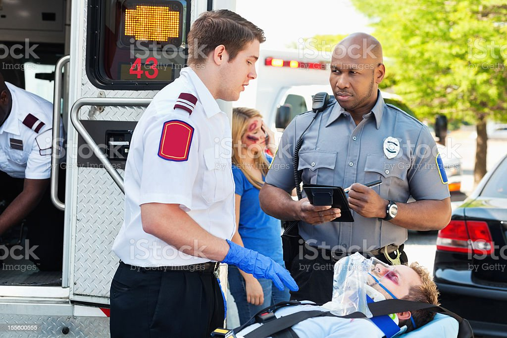 Ambulance medic and police officer discussing accident scene royalty-free stock photo