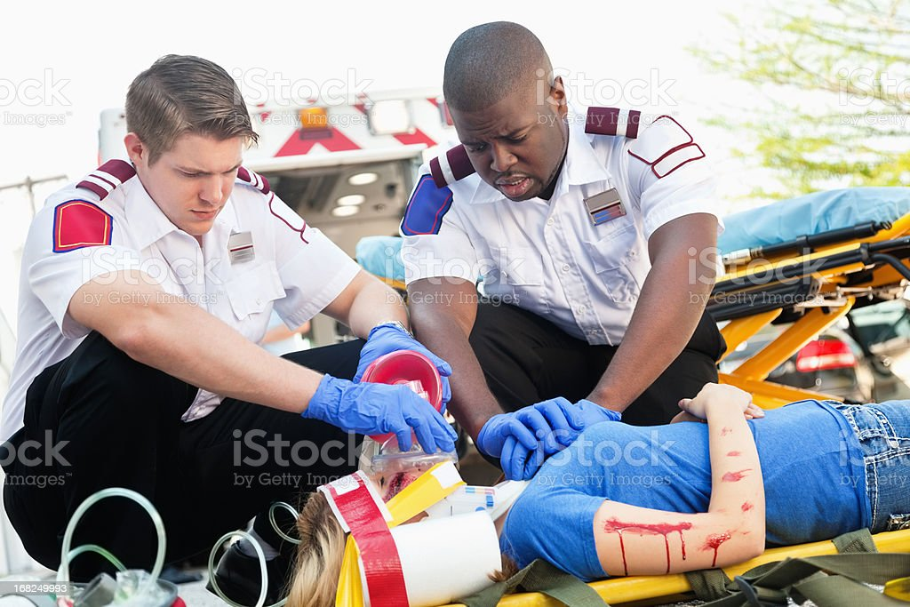 Ambulance medics performing CPR with injured girl on stretcher royalty-free stock photo