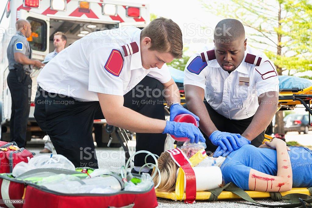 Ambulance medics treating woman on stretcher using CPR stock photo