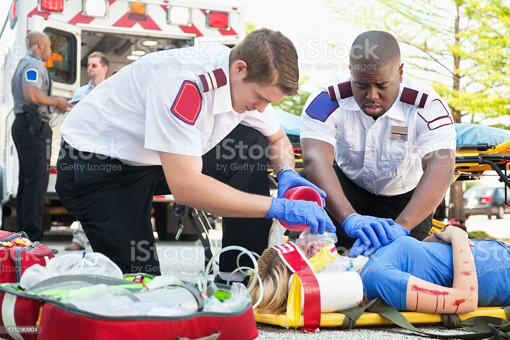 Ambulance medics treating woman on stretcher using CPR stock photo