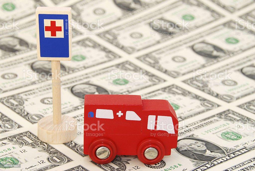 Ambulance (toy) standing on One Dollar Bills stock photo