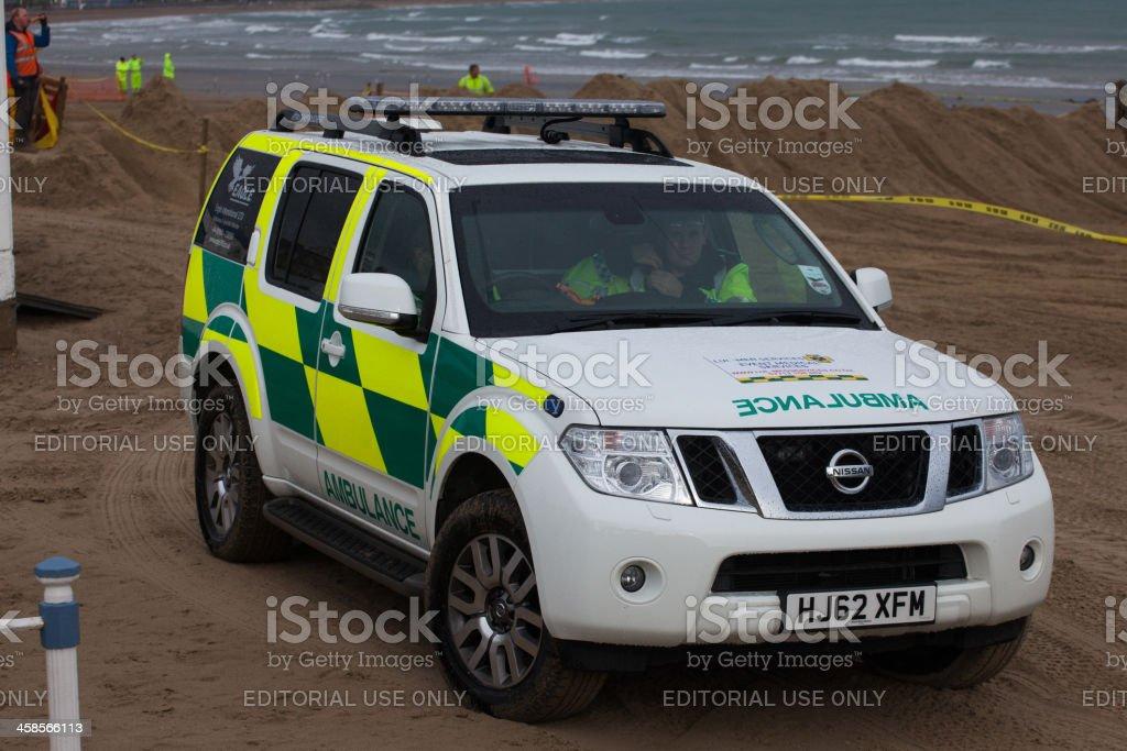 Ambulance waits on the beach at a dirt bike race stock photo