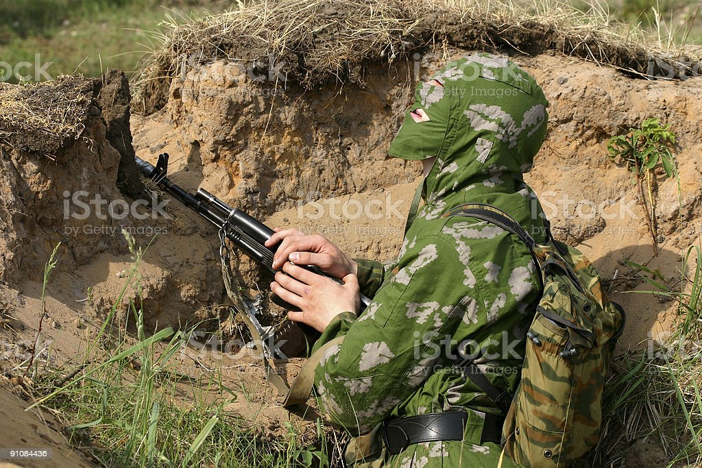 Ambush: soldier in camouflage uniform with Kalashnikov royalty-free stock photo
