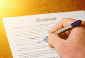 Amending a contract. A male hand makes alterations with pen