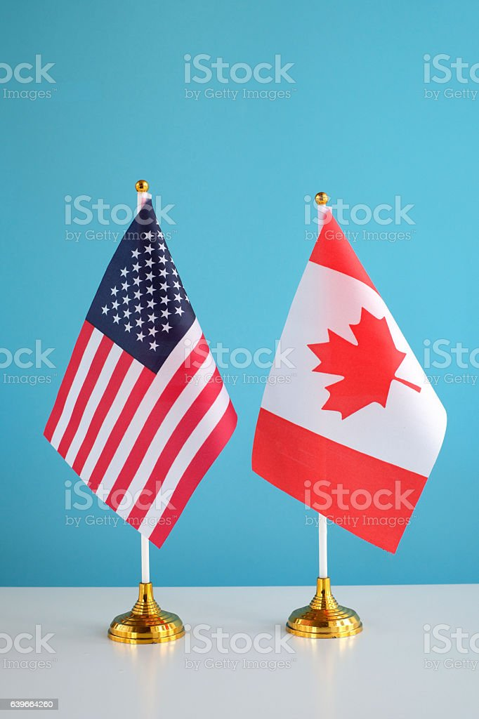 American and Canadian Flags on table stock photo
