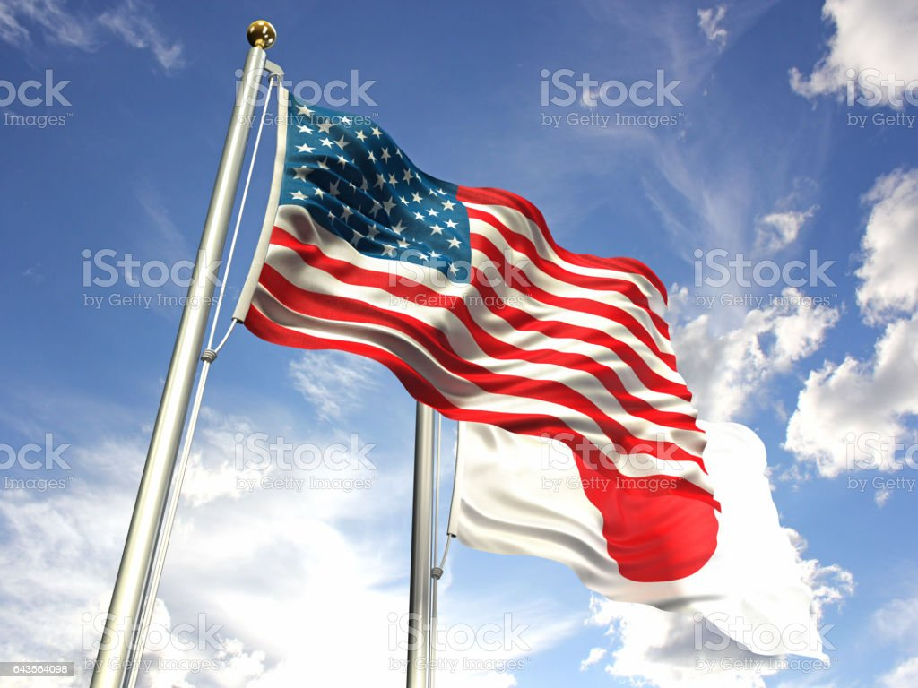 American and Japan flags waving against the sky stock photo
