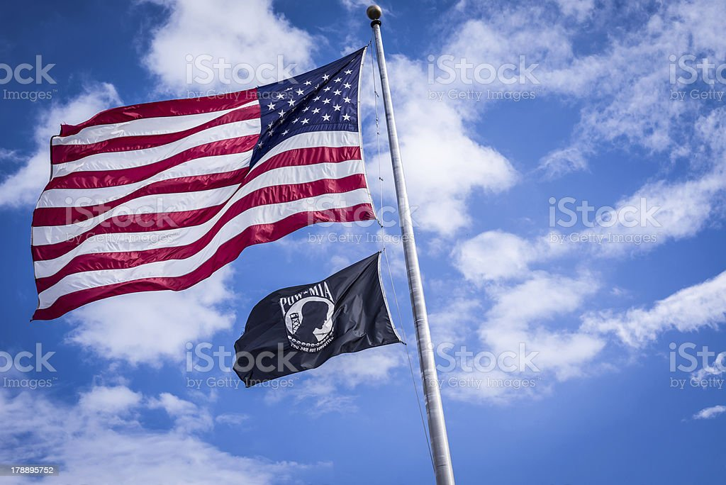 American and Pow flags waiving in wind stock photo