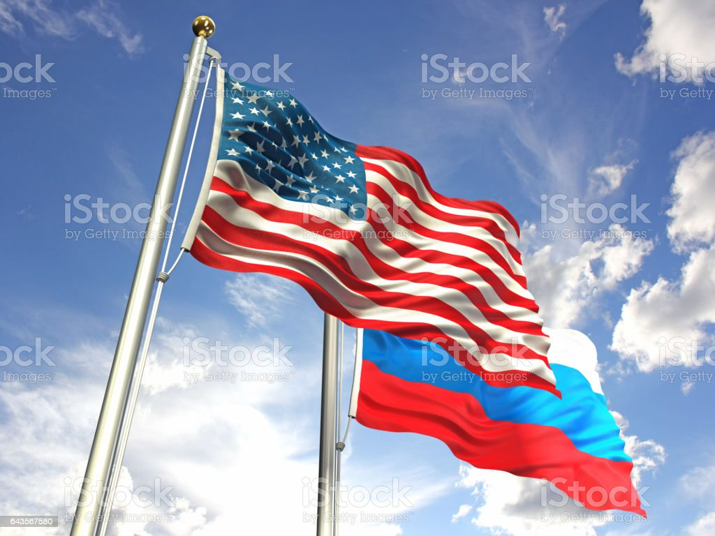 American and Russian flags waving against the sky stock photo