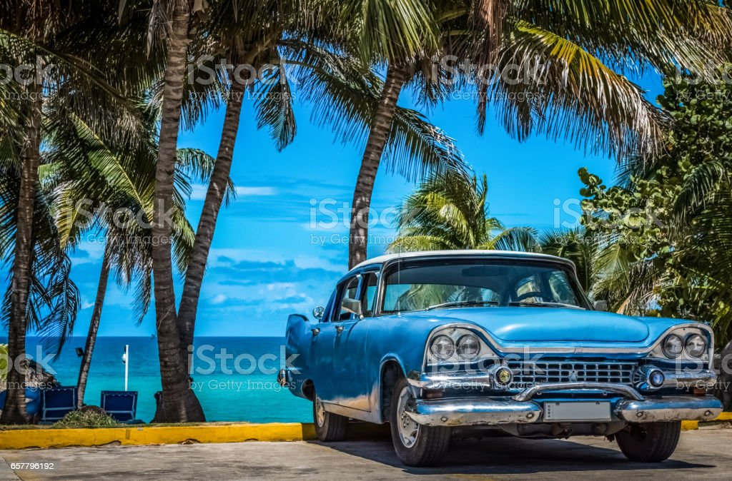 American blue vintage car parked under palms in Varadero Cuba stock photo