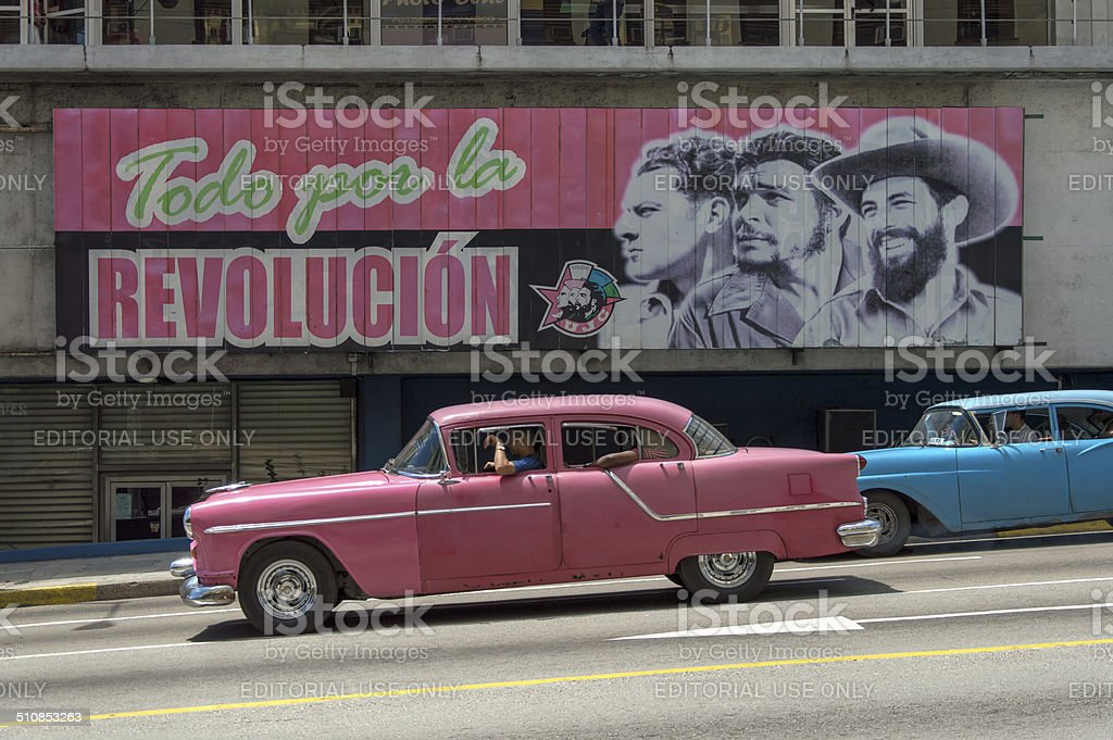 American cars under a cuban propaganda billboard stock photo