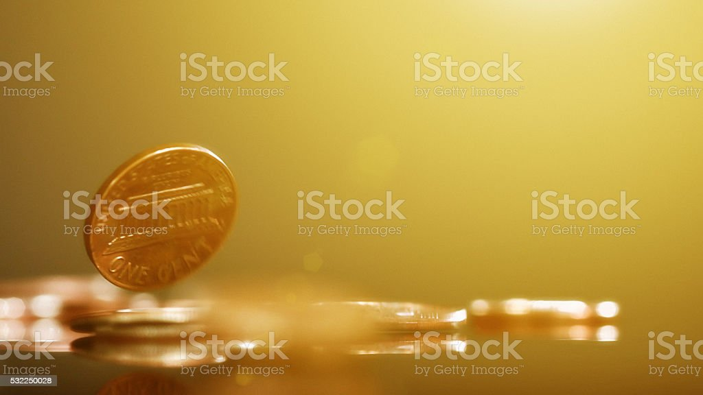 American coins falling against gold-toned background stock photo