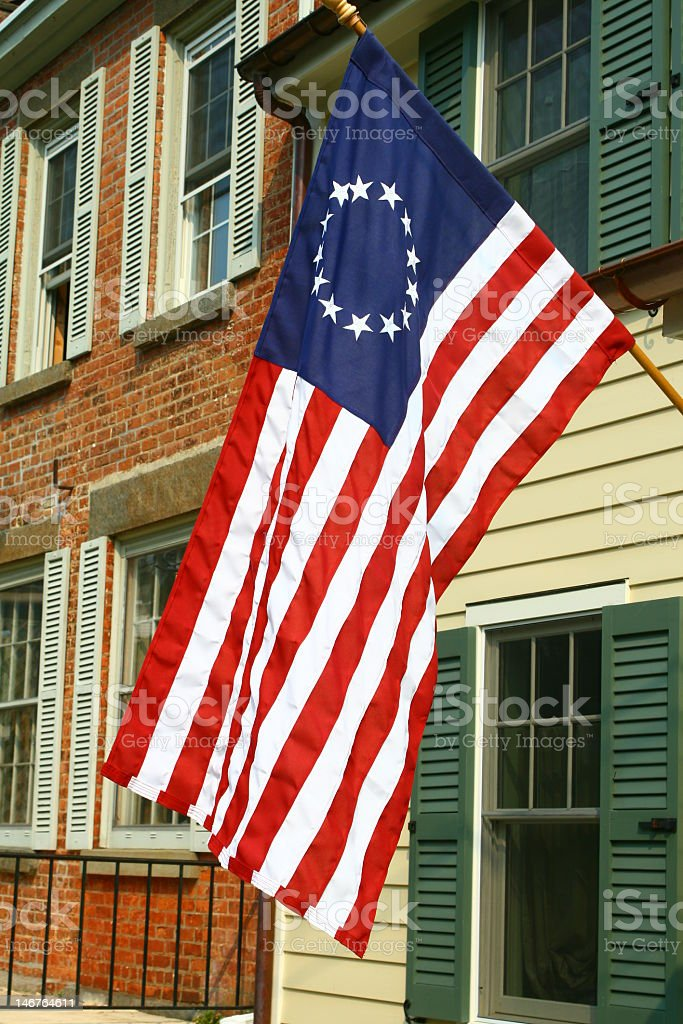 American Colonial Flag Hanging In Front Of Period Homes royalty-free stock photo