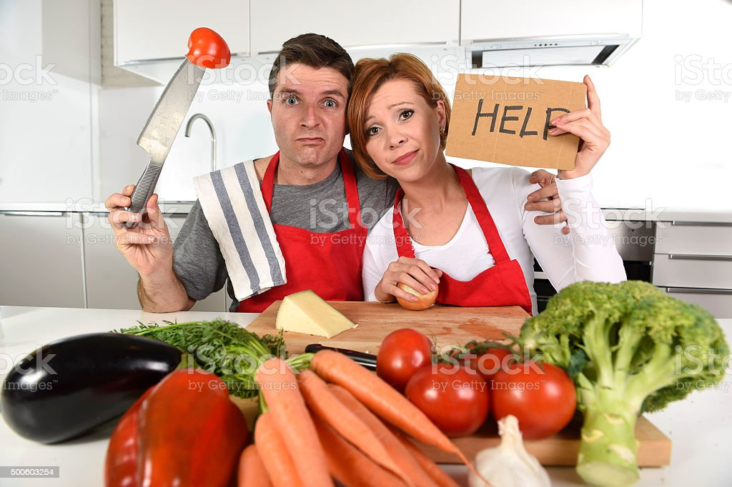 American couple in stress at home kitchen asking for help stock photo
